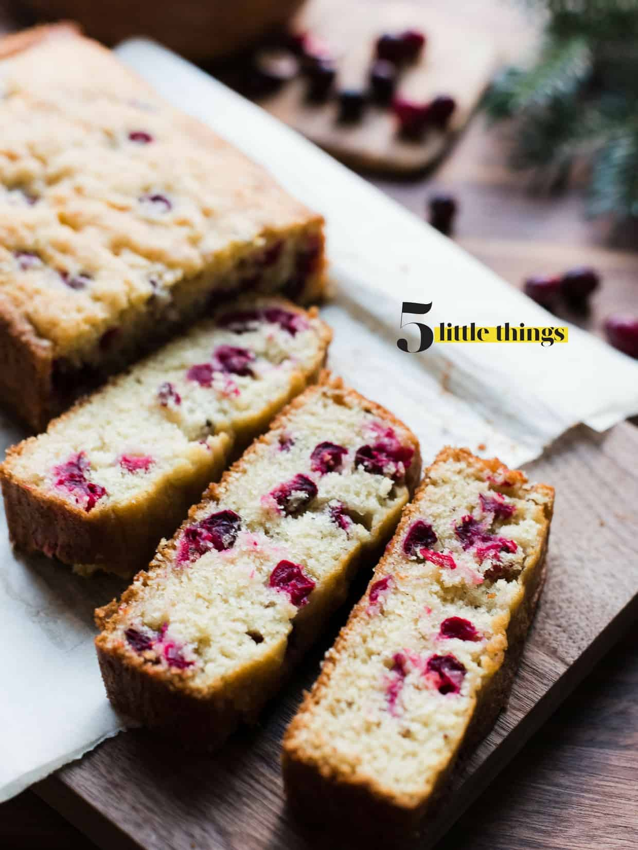A loaf of cranberry bread cut into slices and served on a wooden cutting board.