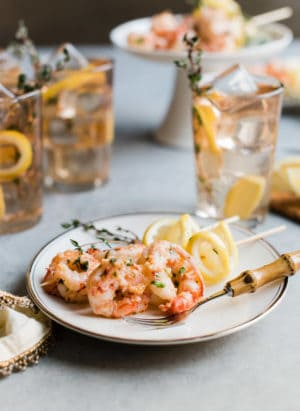 Ginger Lemon Shrimp appetizer served on a white plate with lemon slices.