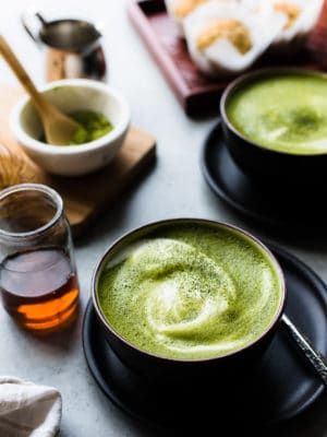 Matcha green tea lattes in black bowls with almond milk, maple syrup.
