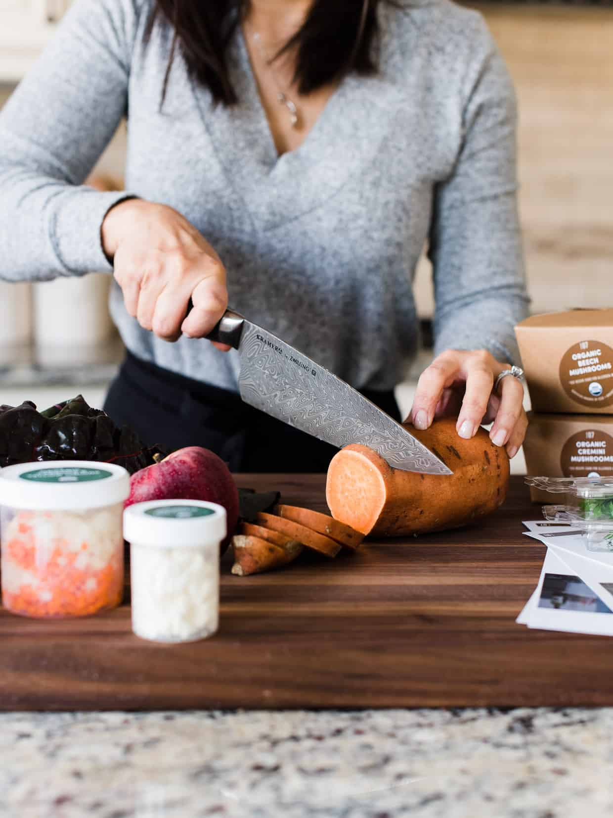 woman slicing sweet potato rounds from Green Chef meal kit