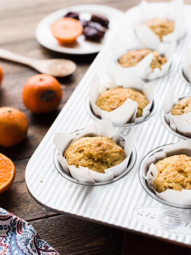 Muffins with mandarin oranges, ginger and dates in a muffin pan.