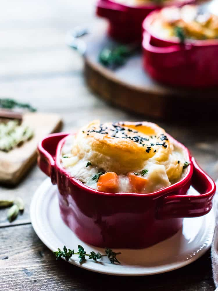 individual serving of chicken pot pie with puff pastry crust in a red serving dish