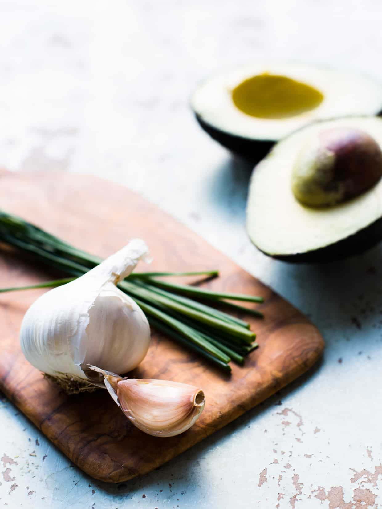 Garlic, herbs, and avocado for Creamy Avocado Green Goddess Salad.