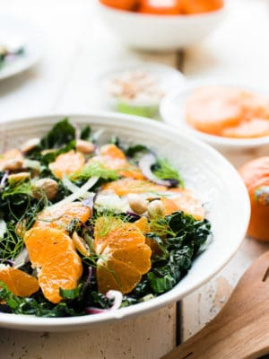 Slices of mandarin oranges on a bed of kale with fennel in Mandarin Orange Kale Salad.