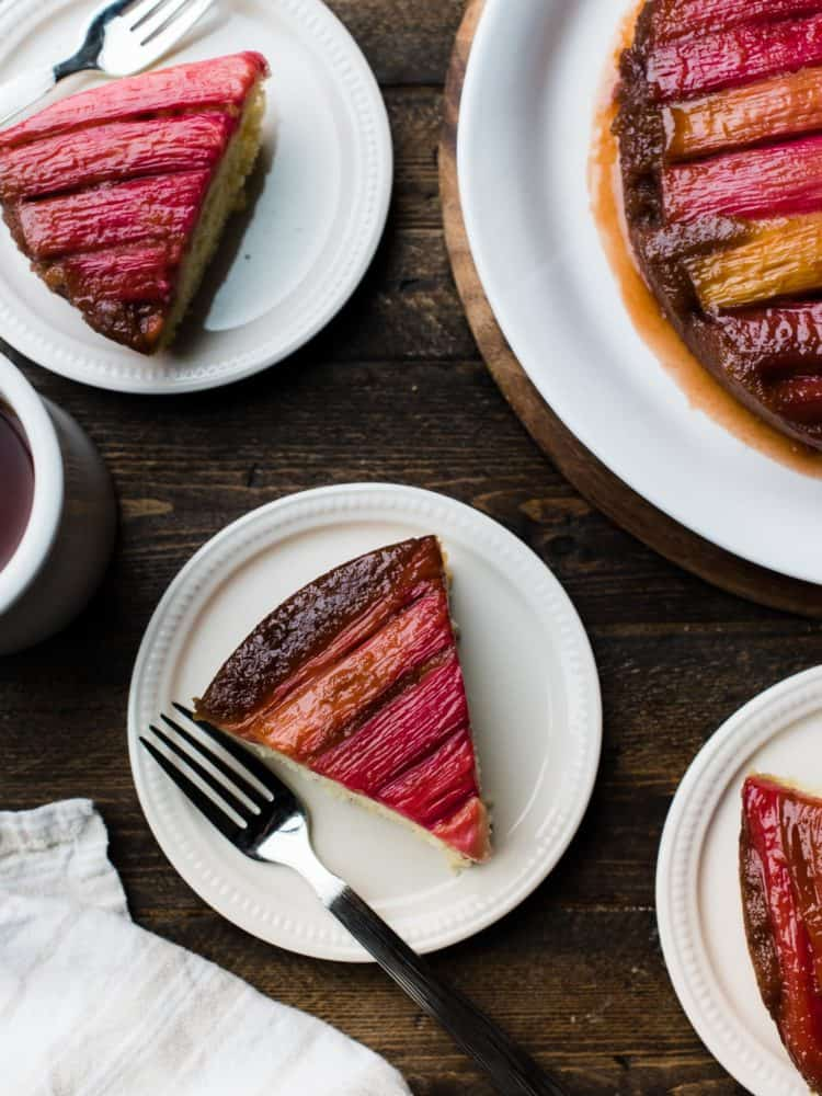 Slices of rhubarb upside-down cake on dessert plates, with beautiful rhubarb stripes.