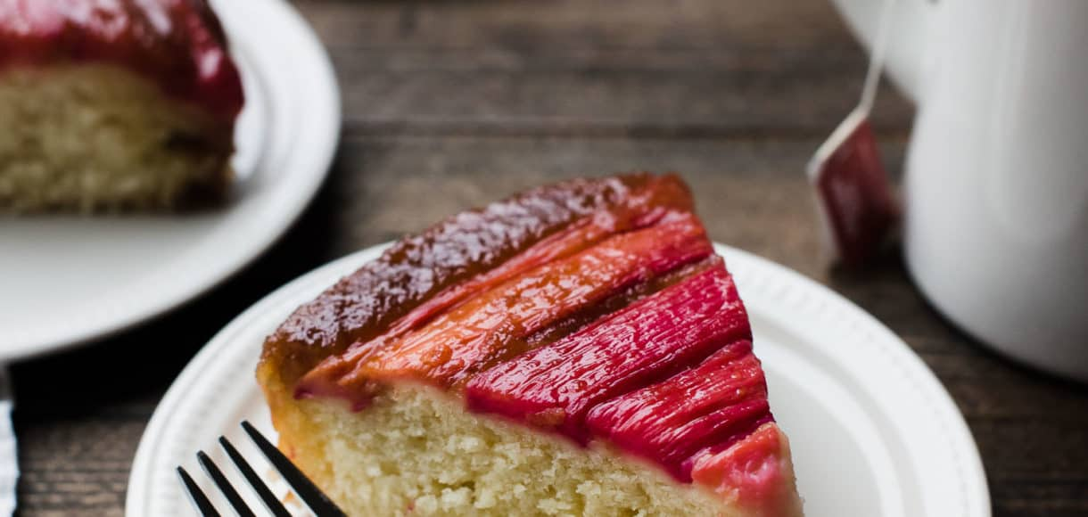 Slice of Rhubarb Upside Down Cake on a dessert plate with a fork and a mug of tea in background.