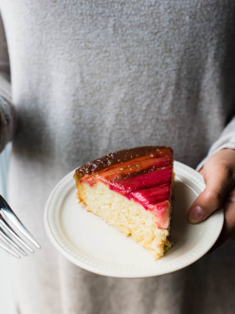 Holding a slice of Rhubarb Upside-Down Cake on a plate.