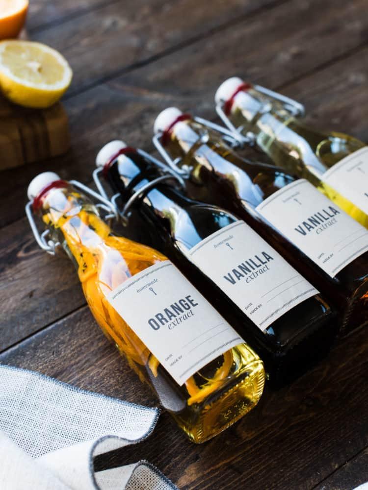 Glass bottles of DIY orange, vanilla and lemon extracts.