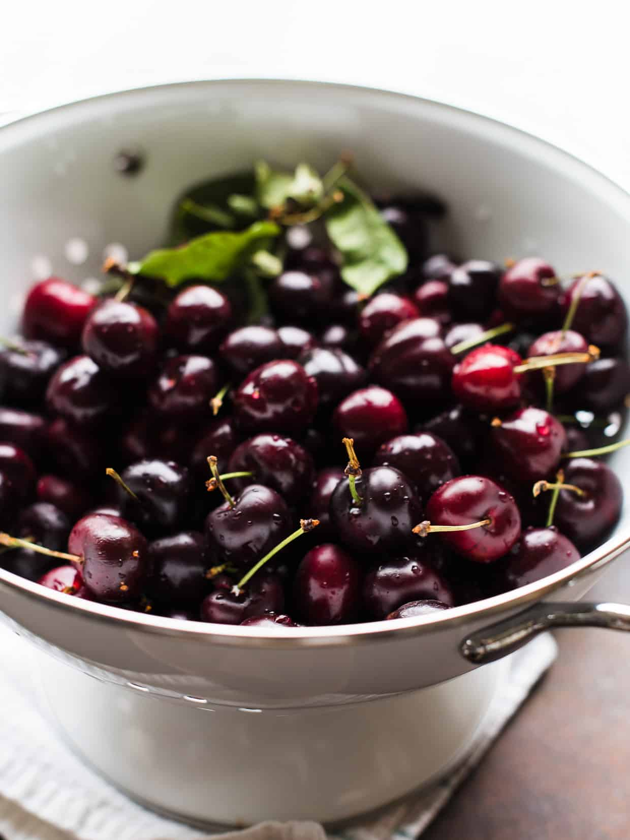Fresh cherries in a white colander.