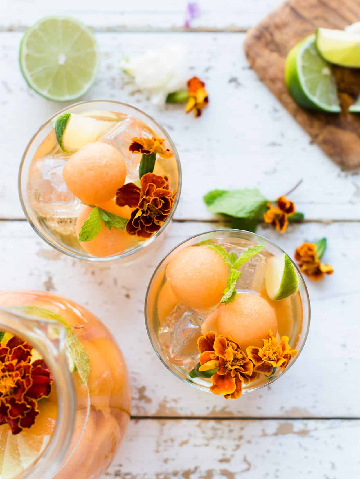Overhead shot of Ginger Cantaloupe Sangria in glasses with edible flowers.