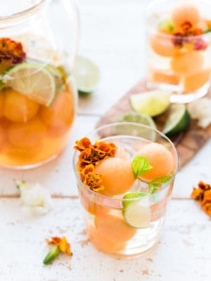 A glass of white sangria with cantaloupe, lime, mint and edible flowers.
