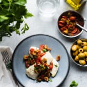 Plate of baked halibut topped with a simple sauce of olives and tomatoes, garnished with parsley.