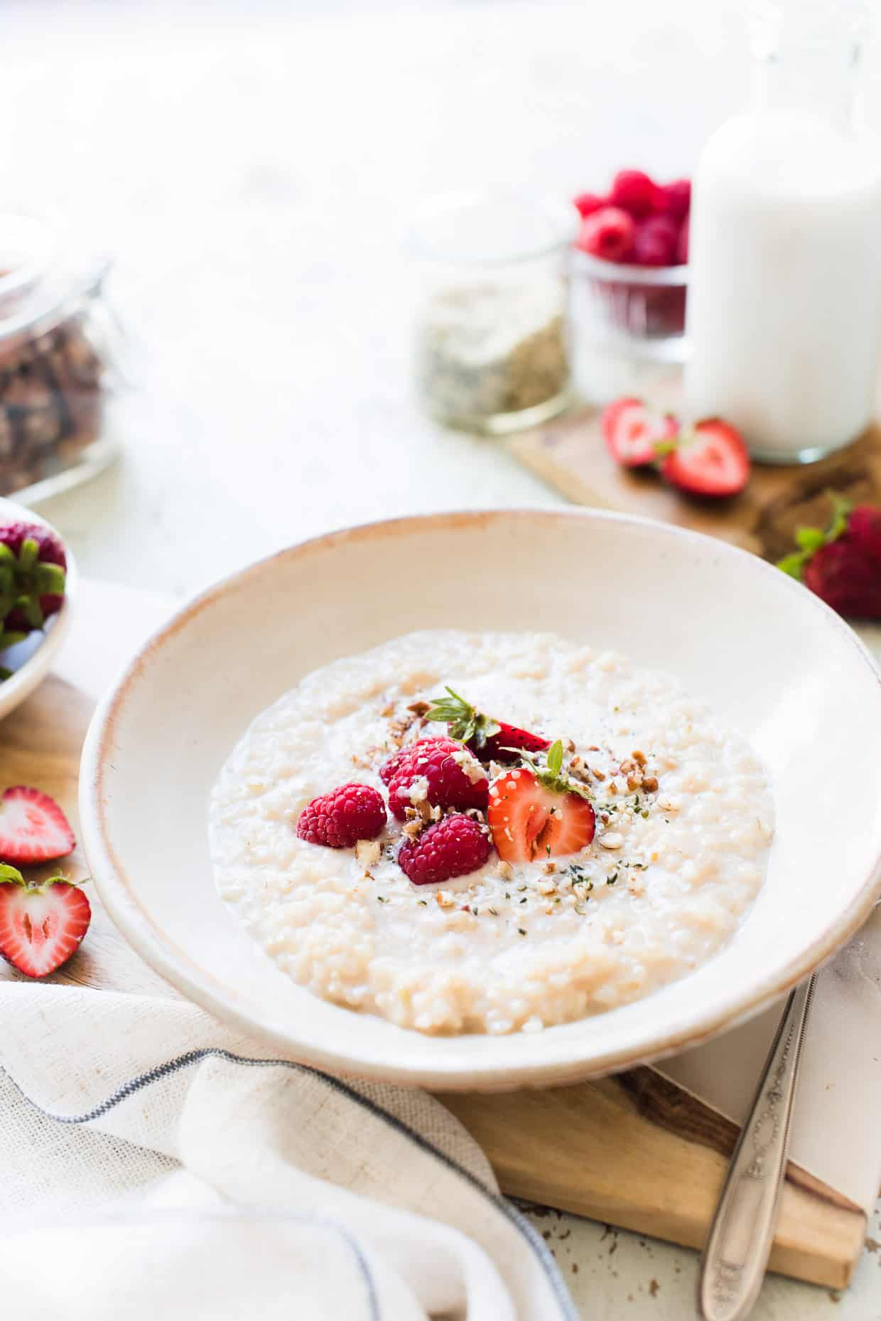 A bowl of Chai Coconut Brown Rice Pudding with nuts and fresh berries.
