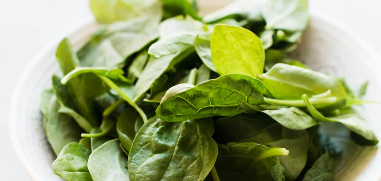 A bowl of fresh spinach on a cloth napkin.