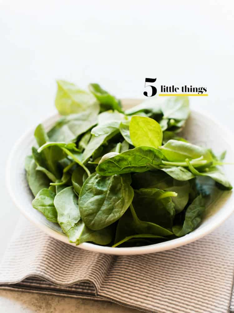 A bowl of fresh spinach on a cloth napkin.