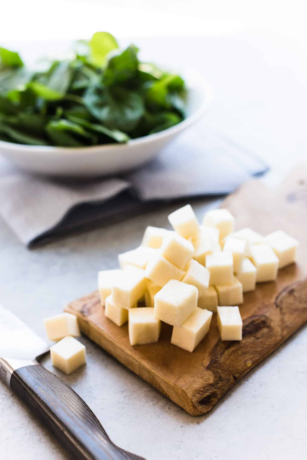 Cubes of paneer cheese on a cutting board.