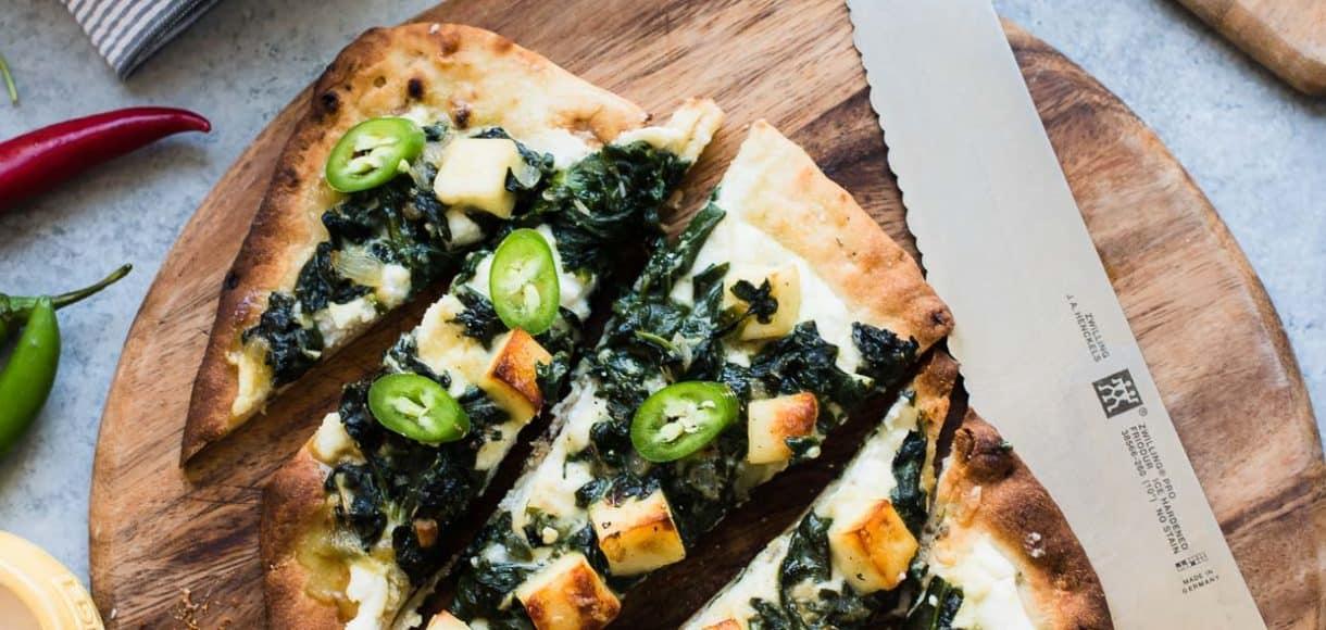 Saag Paneer Pizza sliced on a cutting board.