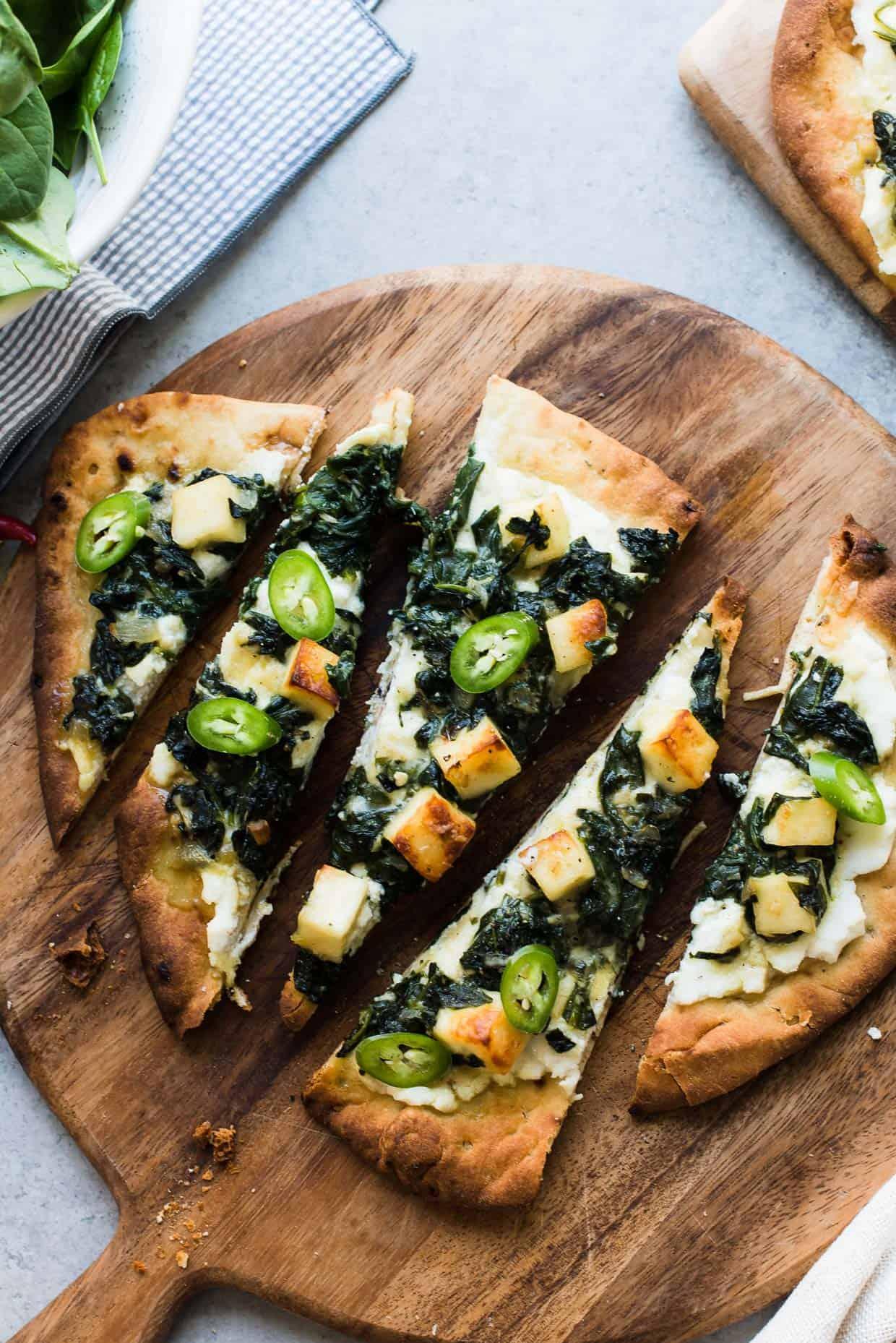 Slices of Saag Paneer Naan Pizza.