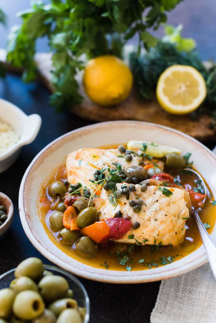 Instant Pot Fish Stew with Tomatoes, Olives and Capers in a cream bowl.