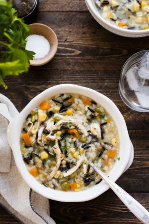 A bowl of Pressure Cooker Creamy Rotisserie Chicken and Wild Rice Soup in a white bowl on wood table.
