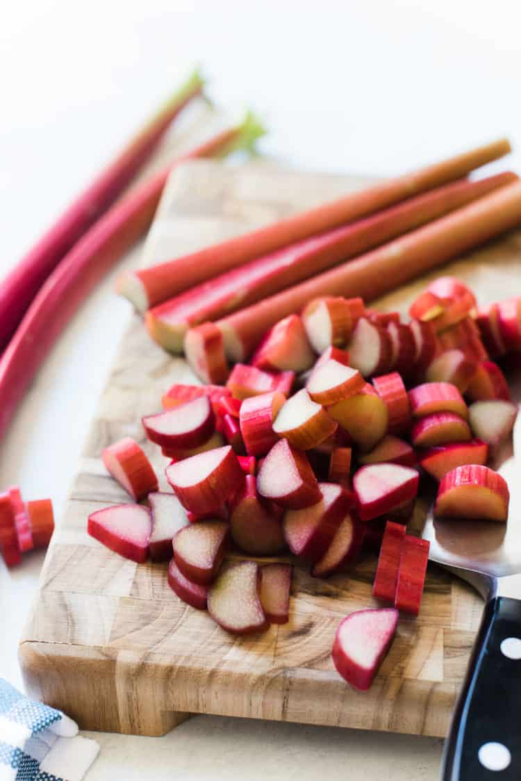 Slices of rhubarb on a cutting board for Rhubarb Frangipane Cake.