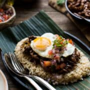 Adobo Loco Moco with shredded chicken adobo on a bed of brown rice with a sunnyside up egg, tomatoes, onions, on a banana leaf.