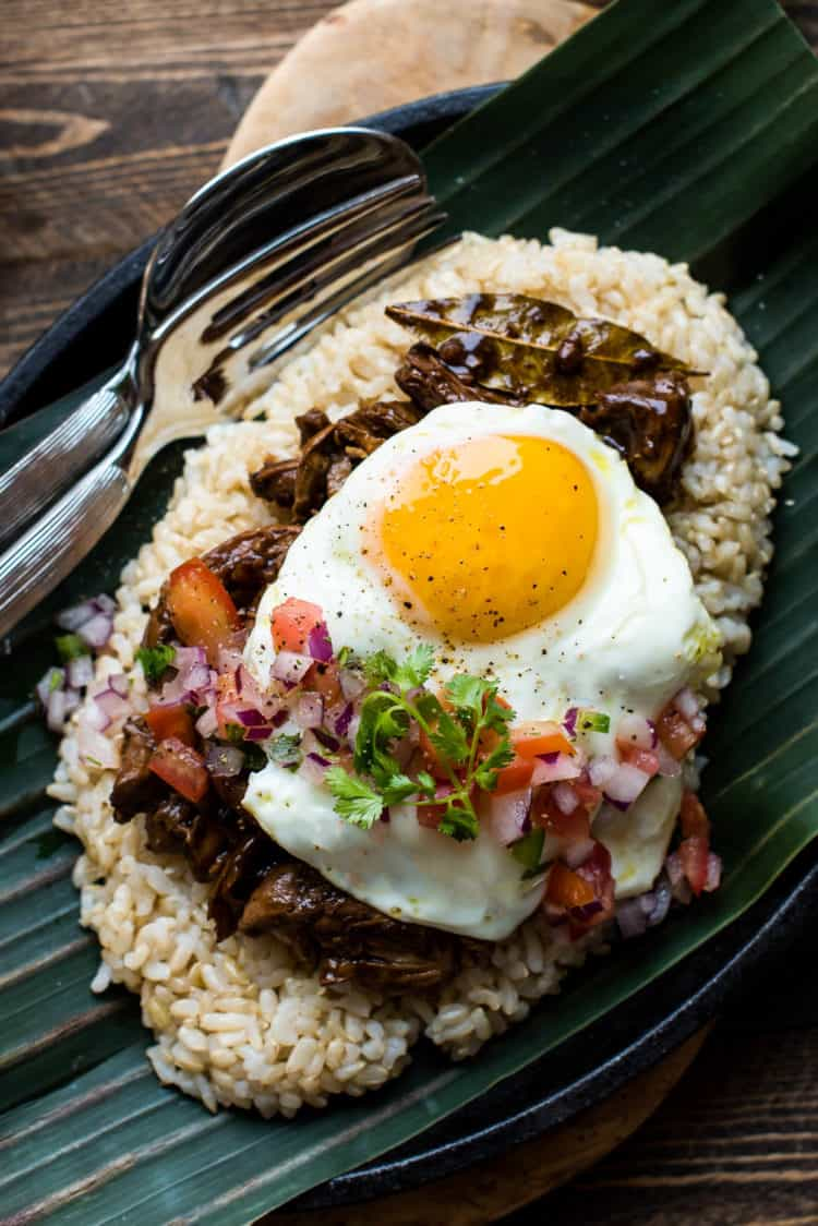 Adobo Chicken Loco Moco on a banana leaf with tomato onion relish.
