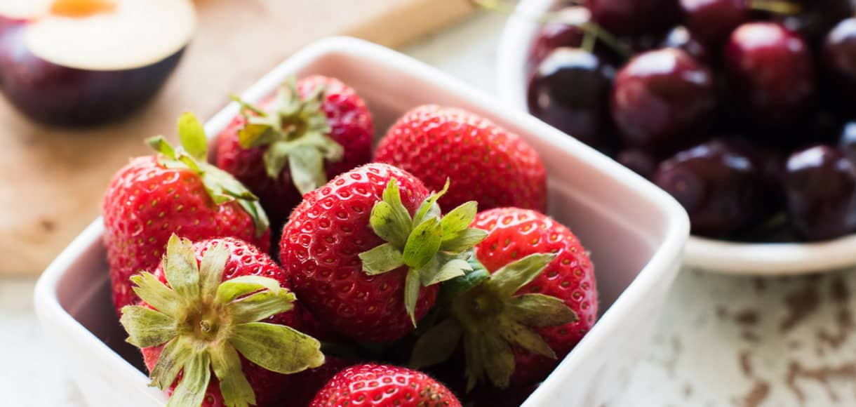 Strawberries in a white ceramic basket, with cherries and plums in the background.