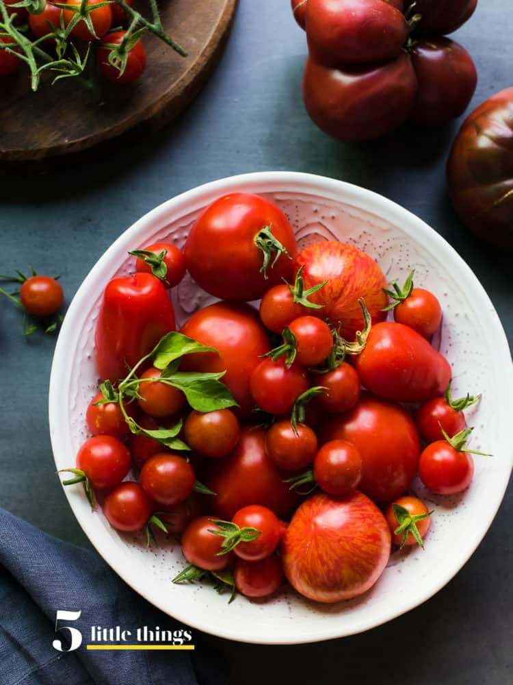 Tomatoes in a white bowl on grey table.
