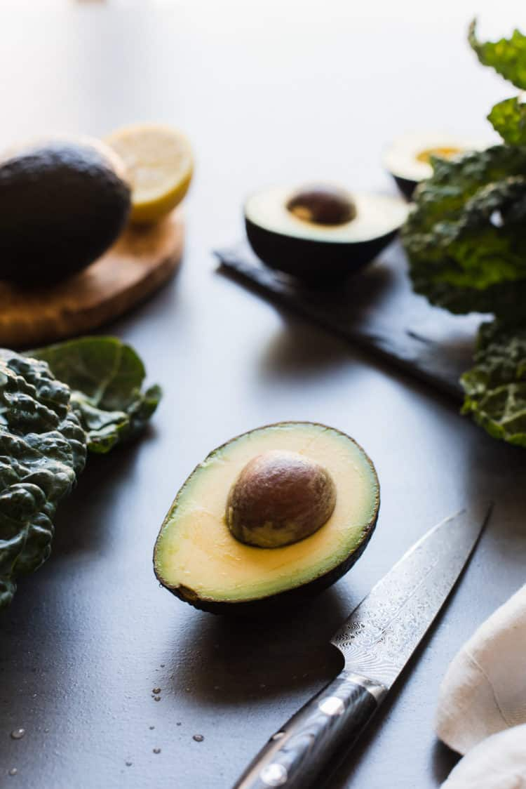 Sliced avocados and kale leaves.