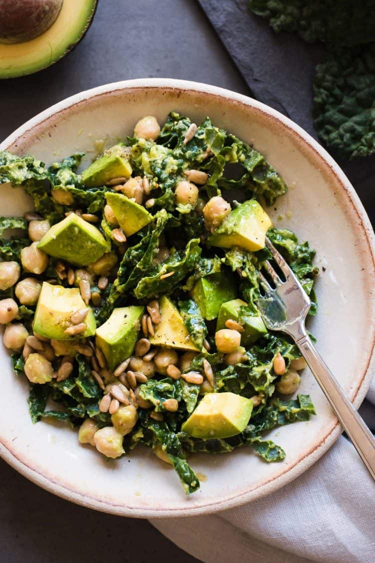 Lemony, Kale, Avocado, and Chickpea Salad in a cream bowl.