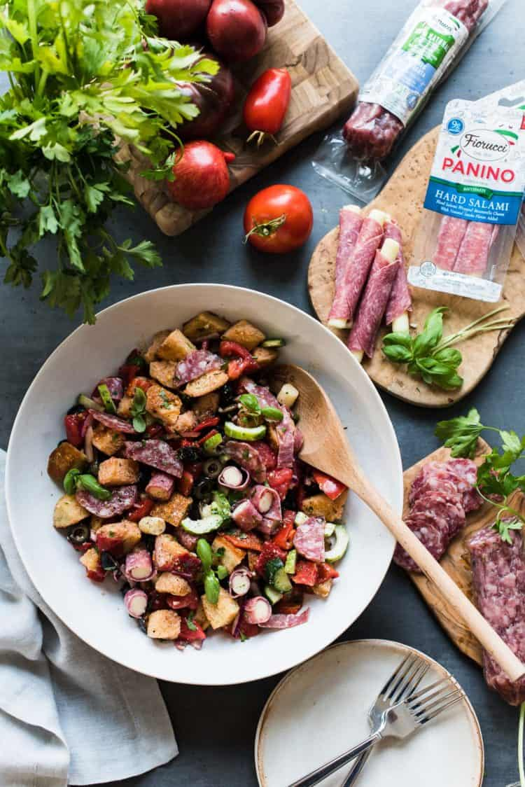 Muffuletta Panzanella Salad in a white bowl with salami and mozzarella on a cutting board.