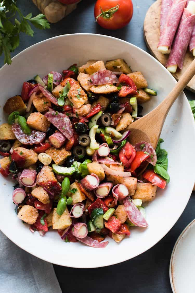 Muffuletta Panzanella Salad in a white bowl with a wooden spoon.