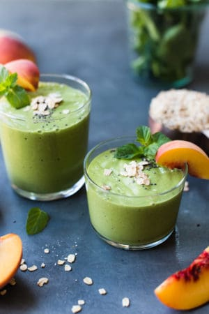 Peaches and Cream Green Breakfast Smoothie in glasses with a wedge of fresh peach, sprig of mint and a sprinkling of oats and chia.