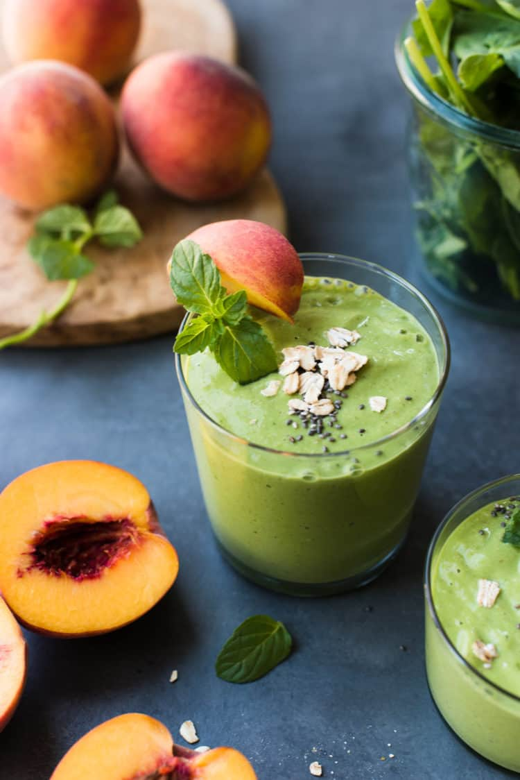 Peached and Cream Green Breakfast Smoothie in a glass with mint and peach garnish.