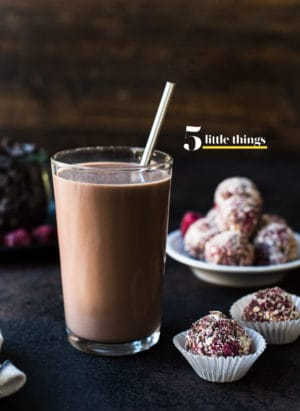 A glass of chocolate milk with a metal straw and energy bites in the background.