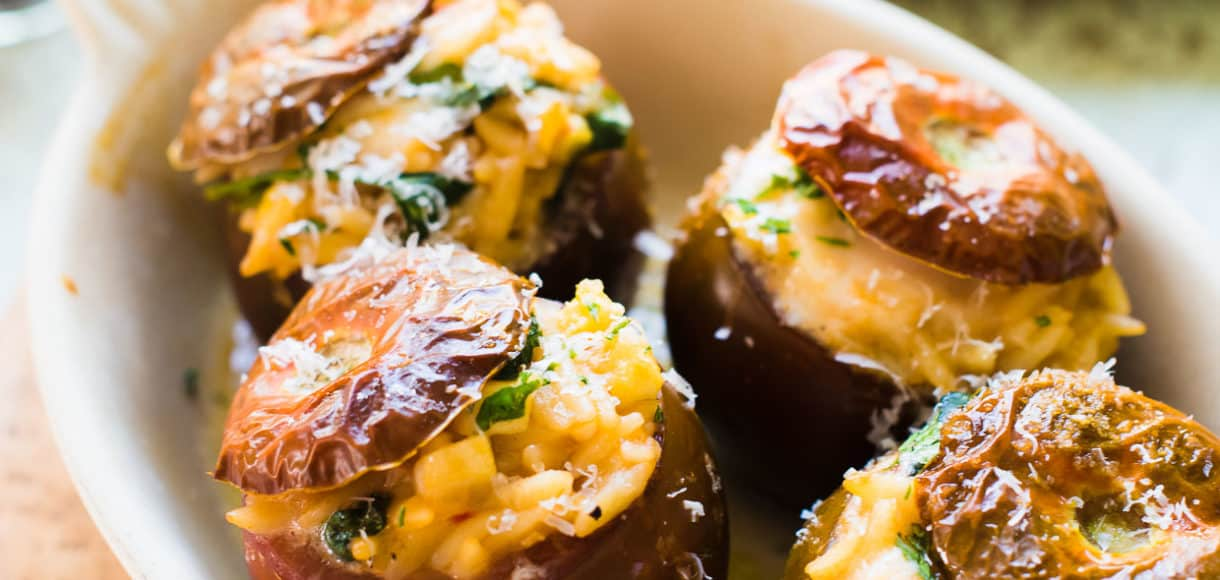 Orzo Stuffed Tomatoes with burrata, parmesan, spinach and yellow squash in a baking dish.