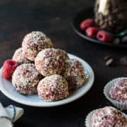 Raspberry Peanut Butter Energy Bites stacked on a dish.