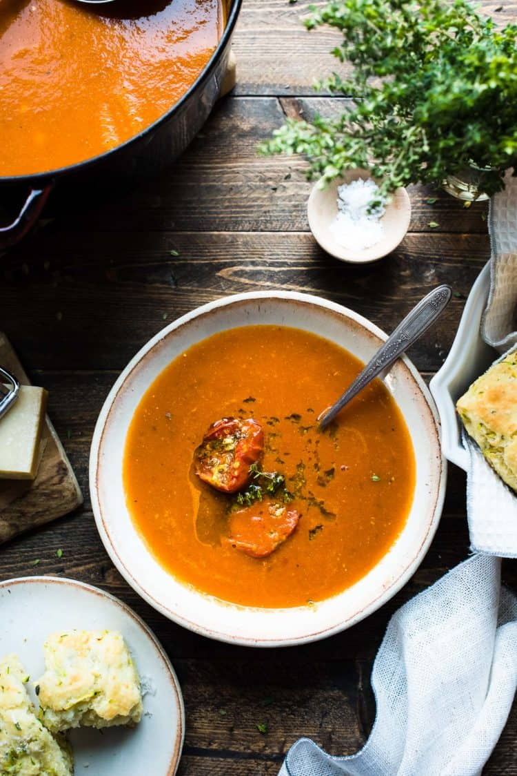 Roasted Tomato, Garlic and Herb Soup in a bowl on a wooden table.