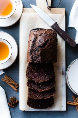 Five-Spice Chocolate Tea Bread sliced on a board with cups of tea on the side.