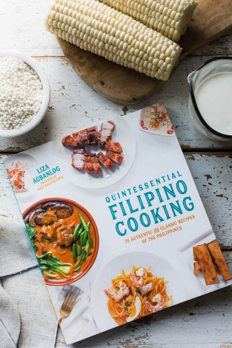 Quintessential Filipino Cooking Cookbook on a white table.