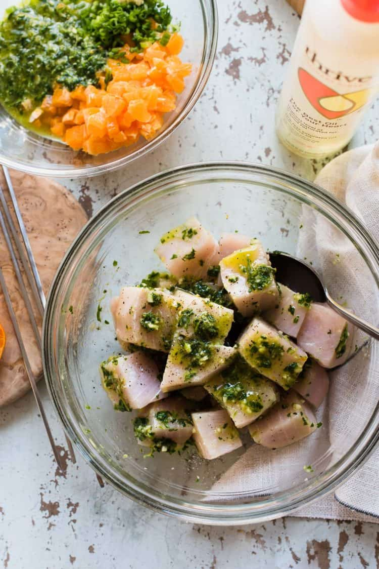Chunks of swordfish being tossed in a marinade.