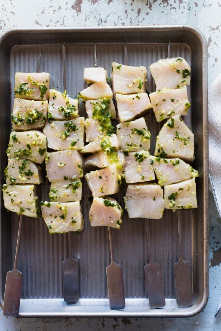 Chunks of marinated swordfish on skewers ready to grill.