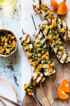 Grilled Swordfish Kebabs with Citrus Herb Salsa on a cutting board with salsa on the side.
