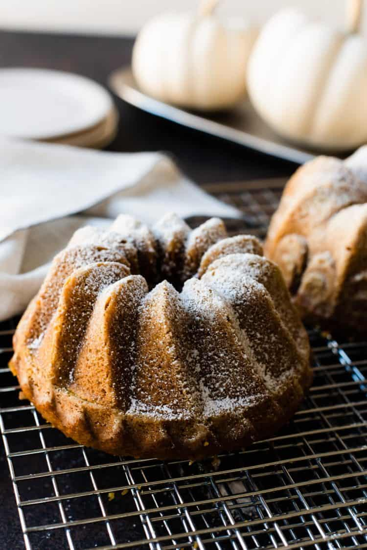 Pumpkin Spice Bundt Cake on a wire rack. White pumpkins in the background.