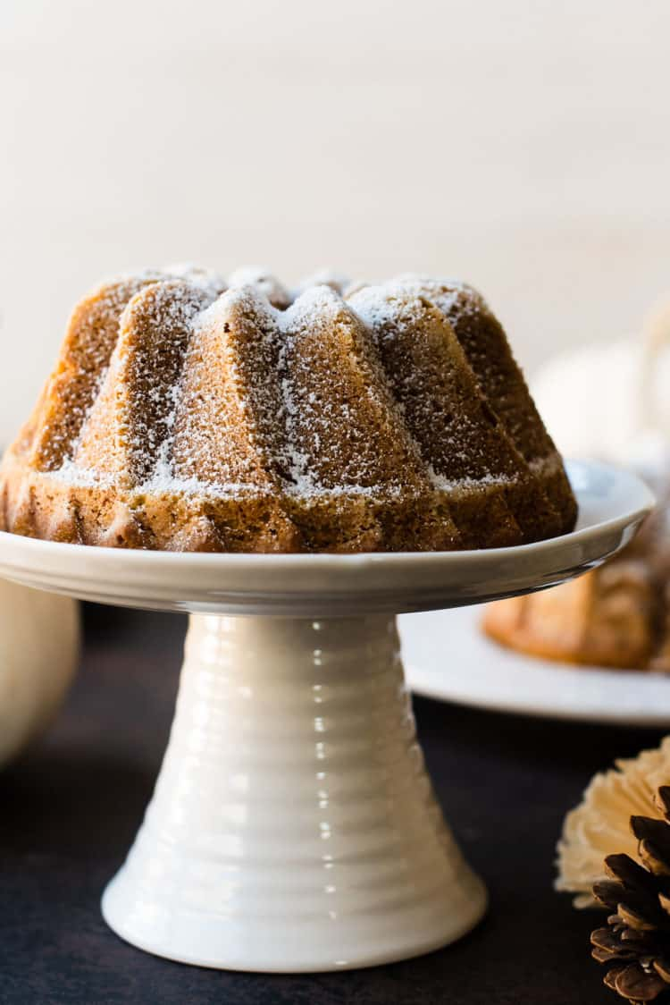 Close up shot of Pumpkin Spice Bundt Cake on a white cake stand.