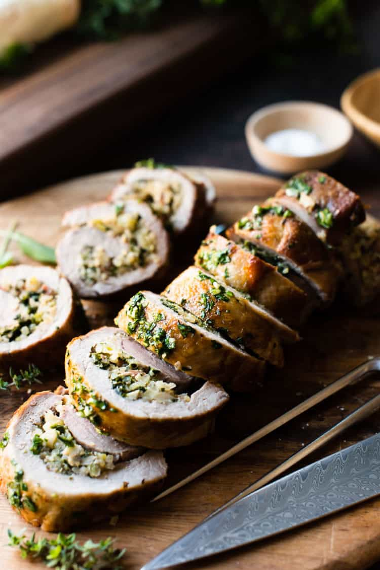 Quinoa Stuffed Pork Tenderloin sliced on a wooden cutting board garnished with fresh herbs.