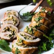 Quinoa Stuffed Pork Tenderloin sliced on a platter garnished with fresh herbs.