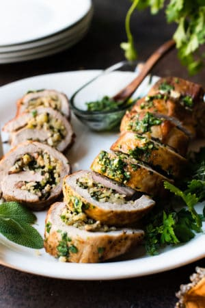 Quinoa Stuffed Pork Tenderloin sliced on a platter garnished with fresh herbs.