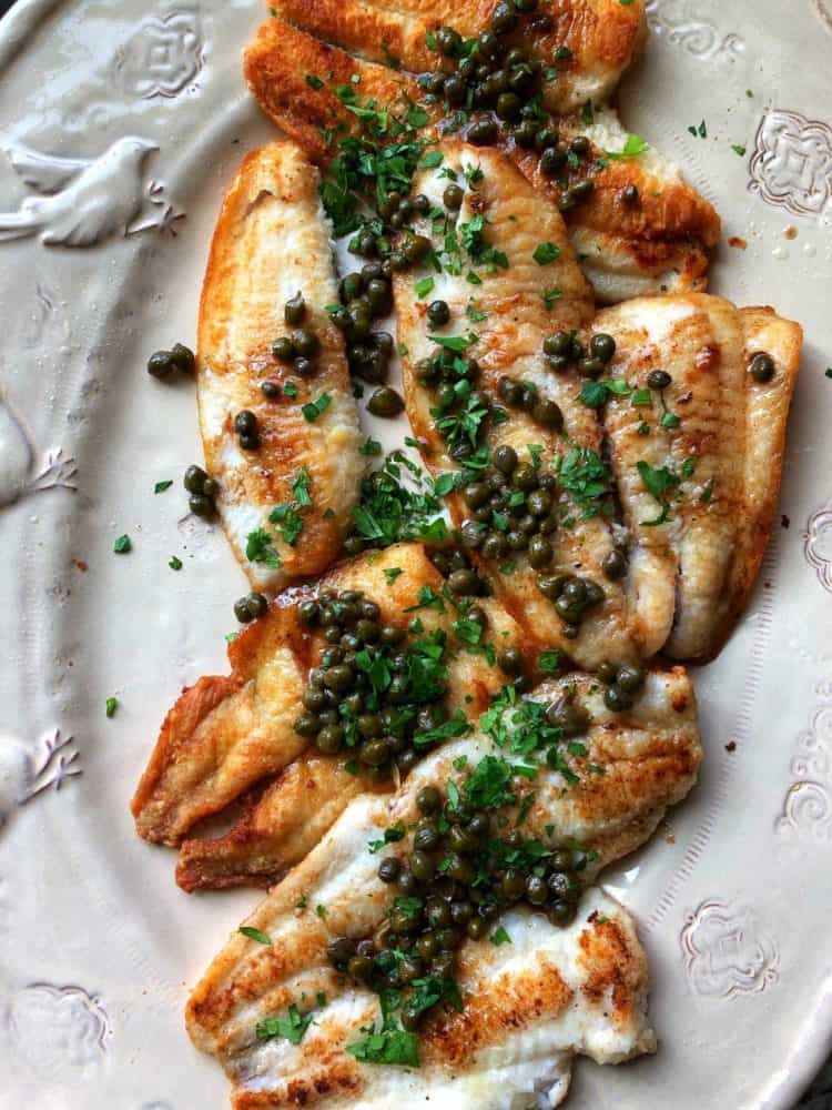 Sole Meunière topped with capers and parsley on a serving platter.